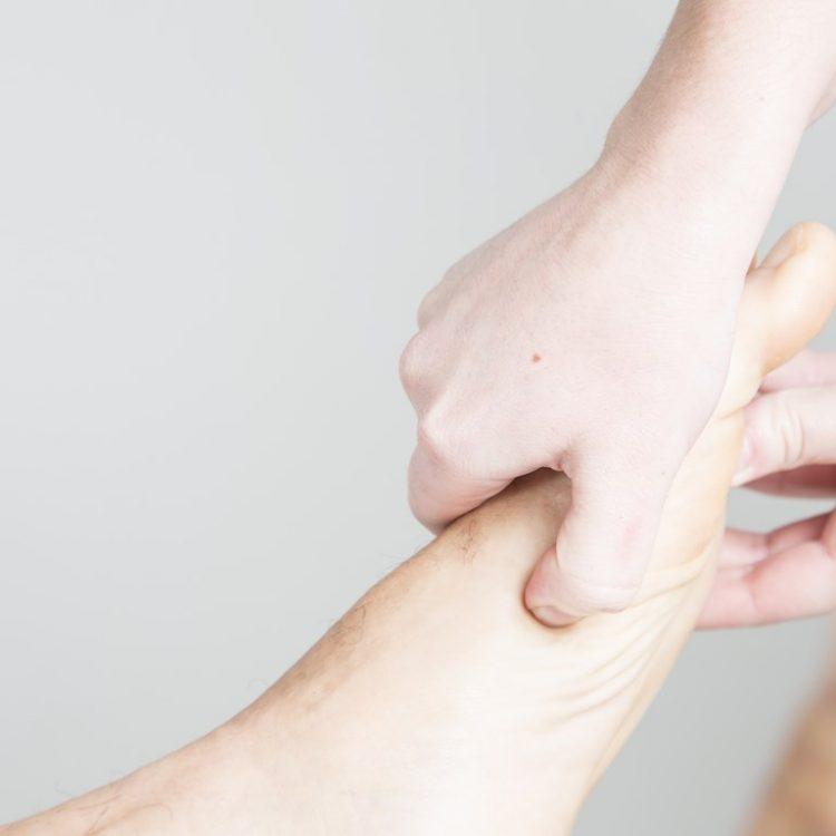 Masaje en el pie aplicando la técnica de reflexología podal.
